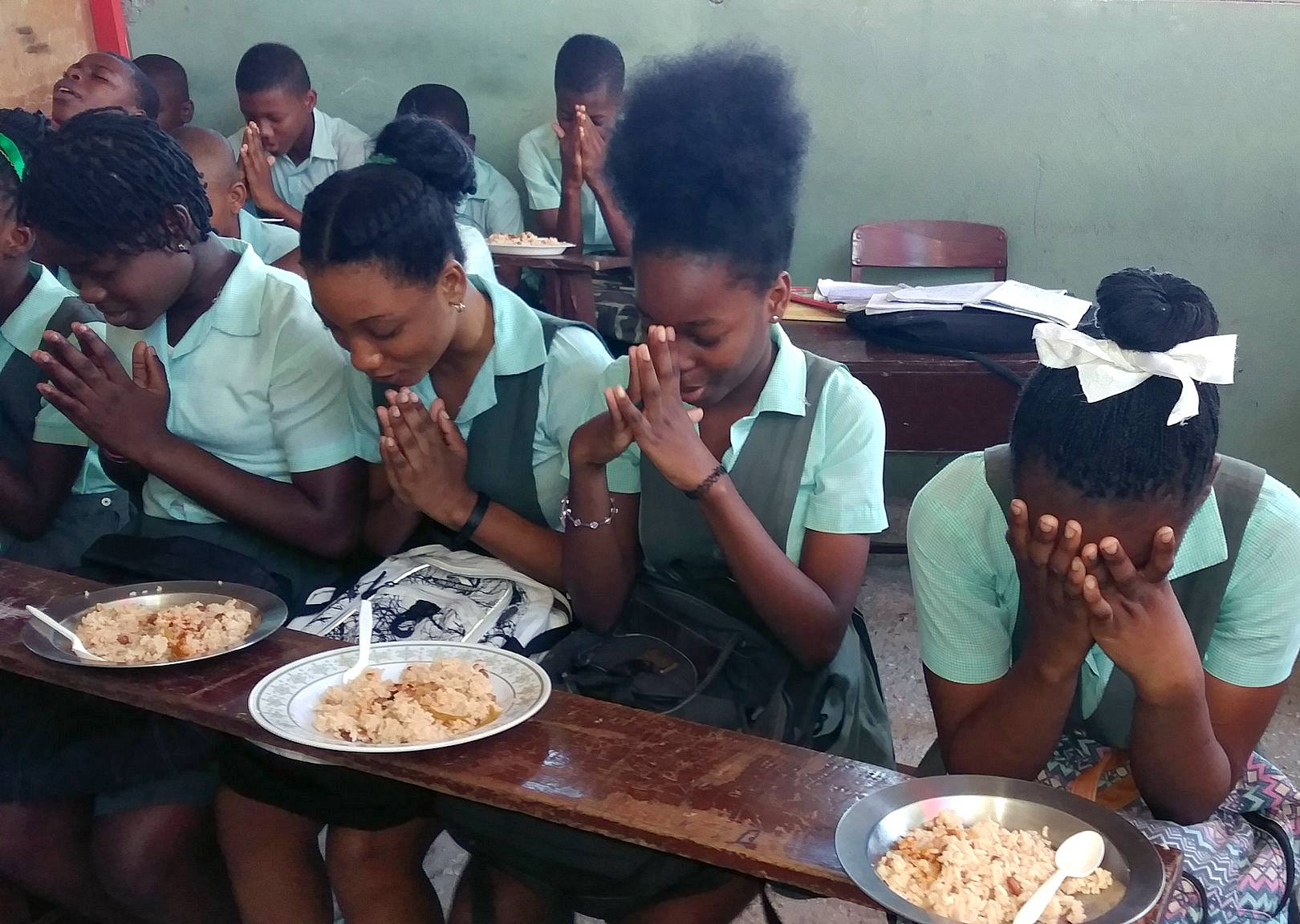 Haitian students praying before meal